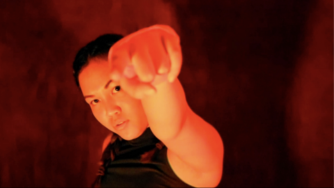 A queer half Chinese, half Malay woman with medium brown skin looks fiercely at the camera, one fist raised in front of her face. Her dark brown hair is in two braids, and she's wearing a black tank top. The lighting is warm, casting an orange hue on her skin, and the background is dark red and black.