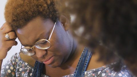 An agender Black person with dark brown skin, short curly light brown hair, wearing glasses, a nose piercing, a ring on their third finger, overalls and a floral grey shirt looks down in frustration. A Black Masc Presenting Womxn to their right looks at them; we can see their hair and part of their neck. The background behind both of them is white.