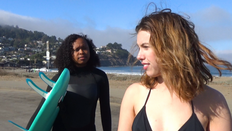 Two women are standing on a beach with blue sky and a hill dotted with houses in the background. On the left, a Black Filipina woman with dark brown skin and curly black hair wears a black wetsuit and holds a bright blue surfboard while looking to the right at a white Latinx woman with light skin and blonde hair. The white Latinx woman is looking to her left and is wearing a black bikini.
