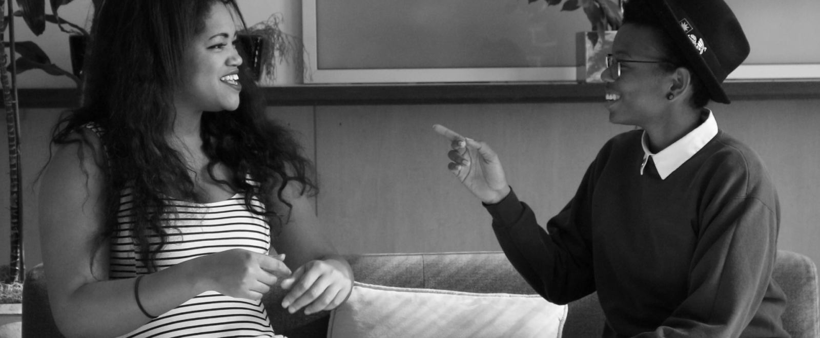 A black and white image of two young Black people sitting on a couch, facing each other and laughing. On the left, a young Black woman with medium brown skin and long dark curly hair wears a striped dress. On the right, a young Black nonbinary person points to their left, wearing a fedora, dark sweater over white button down, and slacks.