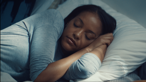 A Black woman with dark brown skin woman lays sleeping on her side in bed with her eyes closed and arms tucked underneath her cheek. A white woman is watching her in the far right of the image; only the tips of her hair, her neck and her shoulders can be seen. The sleeping woman is wearing a grey long sleeved shirt and straight black hair; the pillow she's sleeping on is white, and the lighting casts a grey-blue color on the image.