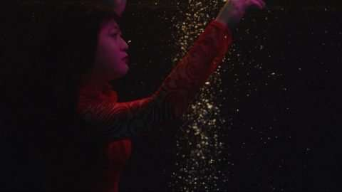 An Asian American woman with light brown skin floats underwater with her arms above her head, looking thoughtfully to her right. She's wearing a knit red turtleneck and red lipstick, and the light casts a purple hue over her face. Immediately to her left is a cascade of golden light, and the background is pure black that blends with her hair.