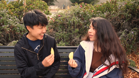 A young Chinese nonbinary person with medium brown skin and short black hair, and a young Latinx woman with medium brown skin and long brown hair sit outside on a black bench, both holding up yellow fruit and looking at one another. In the background there are dark green rosemary bushes with purple flowers, and green trees with red flowers. The young Chinese person is wearing a dark navy windbreaker over a dark blue t shirt with white lettering. The young Latinx woman is wearing a jacket that's blue on the outside and white with red stripes on the inside, and a warm brown shirt.