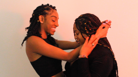 Two Black queer womyn wrap their arms around each other and smile. The womyn on the left has shoulder-length black hair with gold beads, wearing a black tank top and grinning as she puts her arms around the other woman's shoulders. The womyn on the right has long black braids with gold thread, wearing a long-sleeved black shirt while looking down and smiling as she reaches her hand up to hold the other woman's arm. They're standing against a warm beige background with orange lighting.