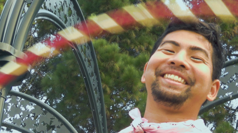 A closeup shot of a gay Japanese American man with medium brown skin smiling at the camera. He's positioned to the right of the image, with short black hair and short beard and mustache, wearing a pink bandana. His head is framed by a pink hula hoop and a green metal arch with dark green leaves and tree branches in the background.