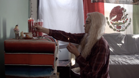 A queer medium brown skin person of Chicanx descent sits in front of an altar, wearing chipped black nail polish, long blonde hair, and a red flannel. On top of the altar is multicolored striped fabric, three red-orange candles, a candle shaped like a bird, several crystals, sage, porcelain bowl and metal tin. The person is holding a lit match in their left hand, and a lighter and one of the candles in their right hand. In the background is a grey sofa, the Mexican flag hanging above it, and white fabric draped to the flag's left.