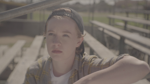 A white nonbinary person with short light ginger hair looks up to their left with a furrowed brow, sitting on bleachers outside. They're wearing a grey and yellow flannel, white shirt, and dark grey backwards baseball cap. One of their arms is bent and resting at a diagonal on the bleacher above them. The background is a green field and sand.