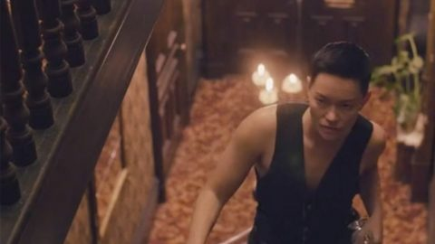 A genderqueer Asian American person with medium brown skin climbs polished wooden stairs, a serious look on their face. They're wearing a low V vest, dark belt, and black jeans, and have short cropped black hair. Their left hand is grasping the banister, and their right hand is at their side, holding two empty glasses. Above them stretches a polished wooden railing, and below and behind them is a warm yellow and red carpet, chandelier, green plant, and two dark wooden doors.