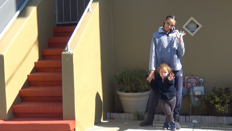 A medium brown skinned mother and child of African descent stand in front of an olive house with red stairs leading up to a steel gate door. The mother wears a light blue sweater, dark blue sweats, and two dark brown braids and stands behind the child, who wears a dark blue jacket, grey jeans, a light blue shirt, and light brown curly hair.