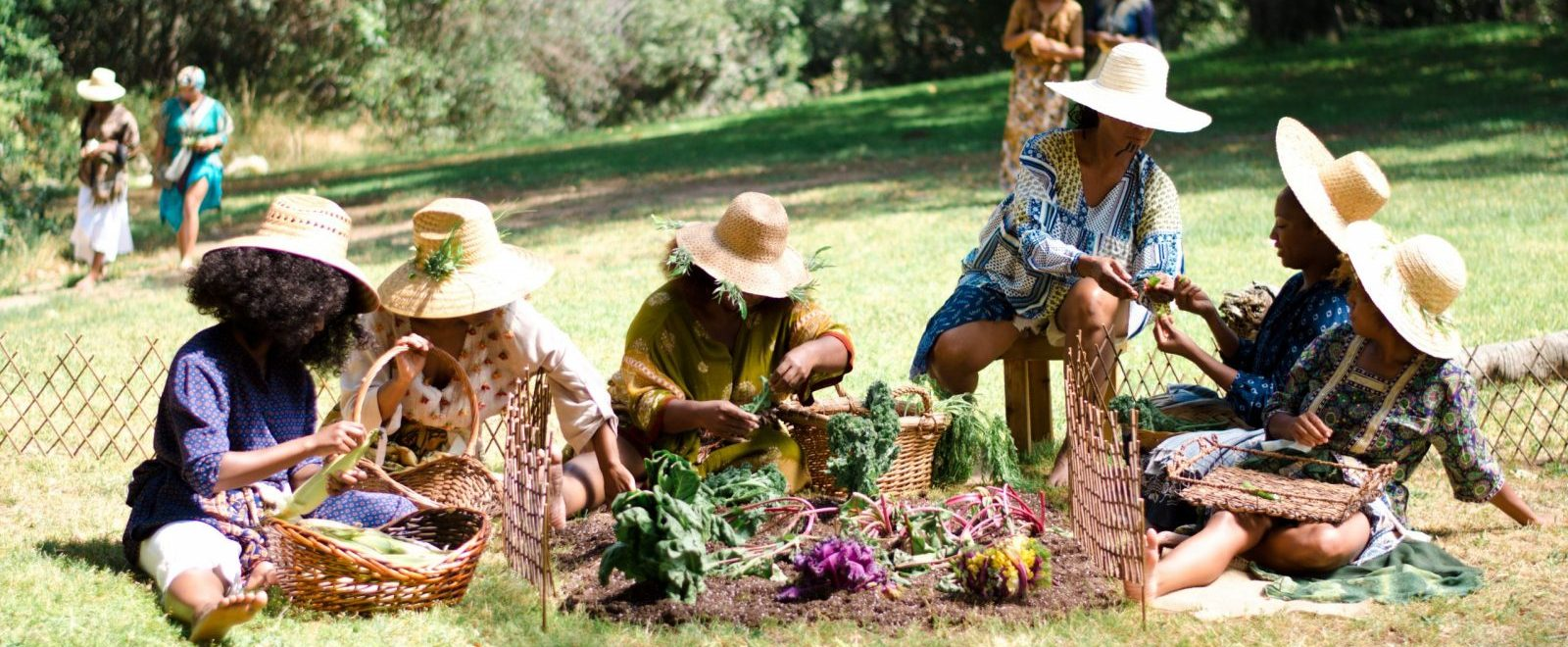 In the foreground, five dark brown skin womyn of Nigerian/African descent, all wearing light woven sun hats with wide brims, sit in grass around a small garden, picking leaves and talking to one another. From left to right: The woman furthest to the left has curly dark brown hair, is wearing purple top with red polka dots and white pants, one leg in front of her and bracketing her basket, looking down at the large light green leaf that she's holding. Next to her is a woman wearing a light top with flower/tassels embroidered on the front, yellow patterned pants, one hand holding her basket and the other reaching across the woman to her left leg into the dirt. In the middle is a woman with green leaves sticking out from the brim of her hat, wearing light green patterned dress with orange trim, looking down at the light green leaf she's holding in both hands. Her arm rests above a basket filled with green stalks poking out of the left side. Next to her is a woman sitting on a stool, black stripes on her chin, wearing a blue yellow and grey patterned loose top and white shorts, holding a plant and showing it to the women on her right. The two women furthest to the right are younger. The one sitting next to the stool is also holding the plant, hat tipped back, looking down and smiling, wearing a dark blue patterned dress, and in her lap is a basket of green plants. The woman furthest to the right is wearing a multicolored dress and in her lap is a basket with only one plant; she has light brown curly hair, one leg tucked underneath the other which is pressed against the garden fence. The garden is full of purple lettuce, red and green chard, yellow and green lettuce. In the background two pairs of dark brown skin women of African/Nigerian descent stand and stroll through the grass. Dark green trees with flowers fill the background.