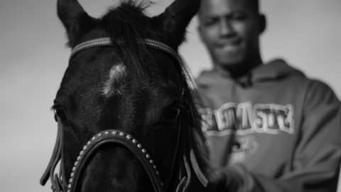 A black and white image of a Black man with dark brown skin sitting on a black horse. The man is on the right side of the image and slightly out of focus, smiling, wearing closely cropped hair and a sweatshirt with bold lettering. The horse is in the left foreground of the image, with a studded leather bridle and a small patch of white hair on its forehead.