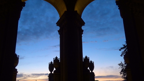 Two archways of the Palace of Fine Arts loom in the early morning light, with stone columns and carved trophies. The top of the sky is dark blue and filled with clouds, descending into a light blue gradient. The sun is beginning to rise, with light orange and pale yellow streaks at the bottom of the arches.