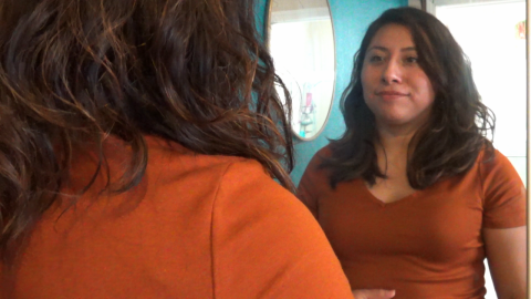 A Latinx woman with medium brown skin looks at herself in the mirror. She has light brown shoulder length hair and is wearing a warm orange shirt. To her left is a bright blue wall with another small round mirror.