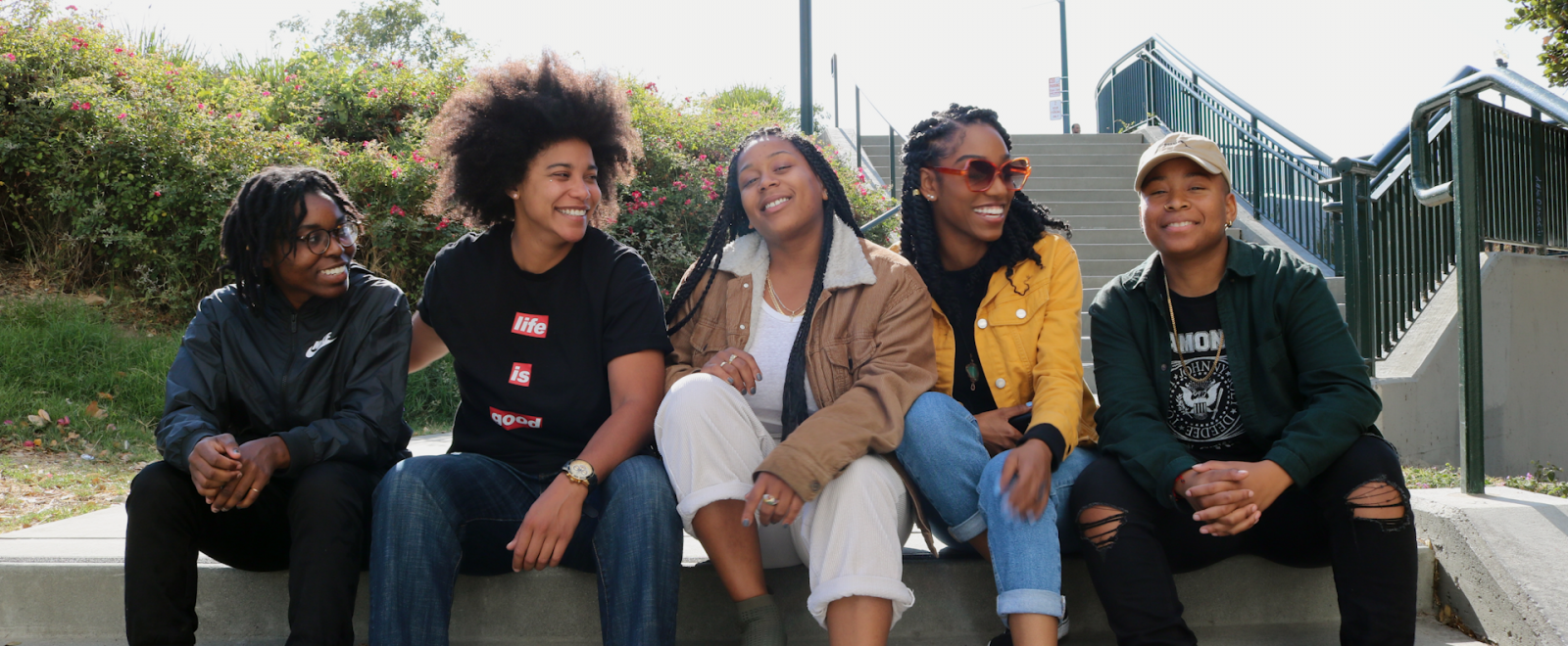 "A group of 5 Black women with dark brown skin and medium brown skin sit on a concrete wall, smiling and laughing while looking at each other and straight ahead. From left to right, a woman with glasses and dark brown hair in short twists smiles and rests their forearms on their knees, wearing a navy windbreaker, black pants, and a silver ring. Next to them, a tall woman with dark brown hair styled into a large natural afro smiles and wraps her arm around the woman to her left, wearing light colored stud earrings, light colored watch, a black shirt with white text on red blocks of color that reads ""life is good,"" and blue jeans. In the middle, a woman with long black brown braids smiles at the camera with her head titled slightly back and arms resting on her knees, wearing multiple light colored necklaces, white shirt, tan jacket, and beige pants. Next to her, a tall woman with shoulder length black twists with gold beads smiles and leans into the woman next to her, wearing large reddish orange sunglasses, small light colored stud earrings, a black shirt, a yellow jacket with large silver snap buttons, and blue jeans. Furthest to the right, a woman with hair hidden under a beige baseball cap smiles at the camera and rests her hands on one knee, wearing small gold earrings, long gold necklace, black shirt with white graphics, dark colored jacket and pants. In the background, there is grass and green bushes with pink flowers on the left, and concrete stairs with green poles and railings on the right."